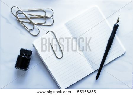 Over head flat lay view of a simple open notebook, pen and ink and paperclips