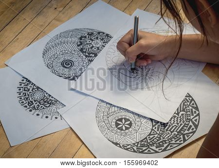 Hand of woman drawing yin yang for adult anti stress coloring book