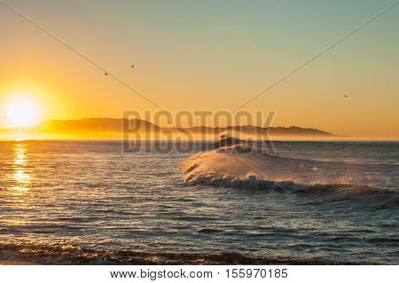 Morning sun glows as east winds blow tops of waves at Ventura beach.