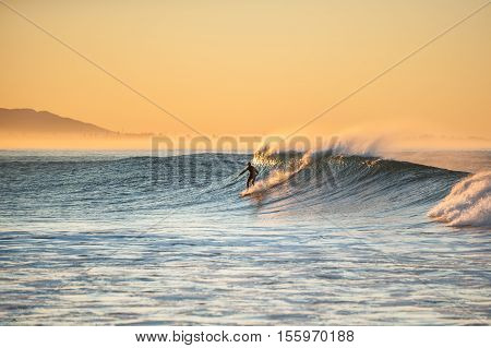 Morning sun glows off surfer as east winds blow tops of waves at Ventura beach.