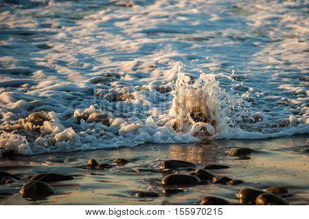 Ocean tide splashing over immovable rock along beach.