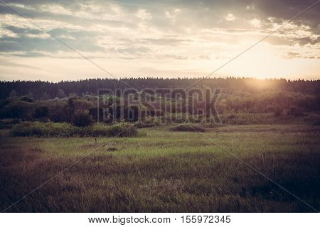 Vintage toned sunrise at summer field in countryside