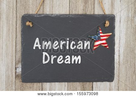 A rustic patriotic dream message A retro chalkboard with a vintage USA star hanging on weathered wood background with text American Dream