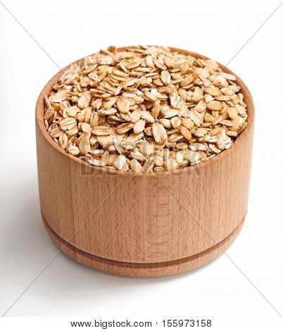 Healthy oat flakes in wooden bowl isolated on white background. Close up high resolution product