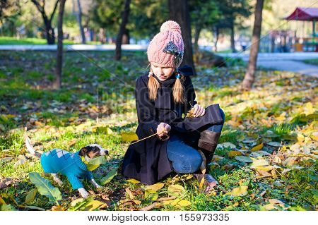 A little blond play girl with her pet dog outdooors in park