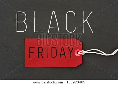 text black friday, the word black written in white and the word friday written in black in a red paper label against a dark gray background