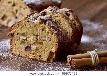 closeup of some pieces of fruitcake for christmas time sprinkled with icing sugar, placed on a wooden rustic surface