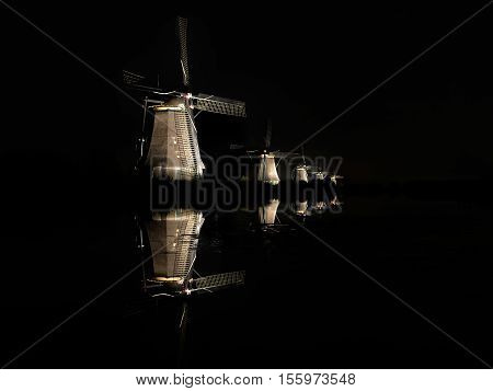 Five illuminated windmills lighted by floodlights with reflection in the water of the canal in the dark black night creating an almost surreal landscape in Kinderdijk the Netherlands.