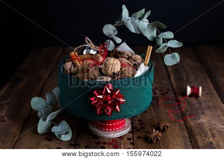 A Decorative Festive Centrepiece Full of Walnuts, Cinnamon Sticks, Star Anise and Christmas Decorations on a Rustic Wooden Table.