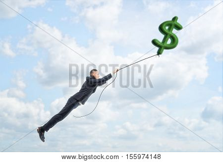 A businessman floating up in the sky holding a big dollar sign on a string. Way to success. Earning money. Business and finance.