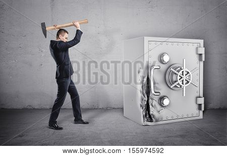 A businessman holding a hammer over his head, and a safe with its door broken, all isolated on the grey background. Breaking the law. Theft and property crime. Money problems.