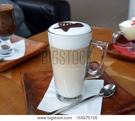 Latte Macchiato On Glass Cup On A Wooden Table