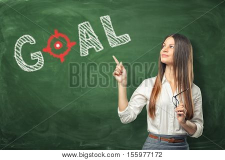 A young woman holding her glasses and pointing the finger at the word goal written on the green chalkboard wall. Set a target and and keep trying until you reach it. Dedication in discharging important tasks. To face the future.