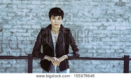 Young woman with short stylish hair in urban setting wearing leather jacket