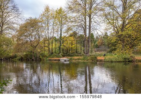 Autumn trees reflected in the lake with a boat resting near the shore