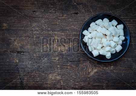 White mini marshmallows in a black plate on a wooden background with place for text. Different mini puffy marshmallows. Marshmallow concept. Top view. Copy space.