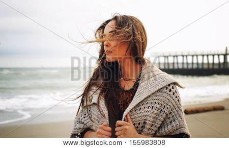 Fashion woman portrait against a pier on a sea beach, autumn outdoor fashion, windy day