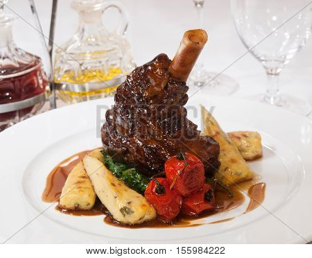 Lamb knuckle with thyme gravy roasted potato sticks (dumplings) and spinach leaves