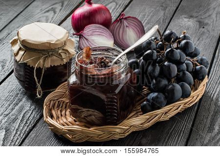 Red onion jam (onion confiture) with grapes in glass jars and ingredients for its preparation in a wicker basket on a wooden table. French cuisine. Selective focus