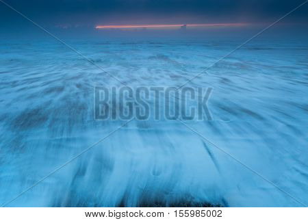 Soft focus blue ocean wanes at the beach at sunset