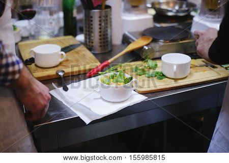 Chef preparing a meal with parsley, onion, eggs, vegetables at restaurant kitchen. Food on dish before it goes on the table. Culinary workshop, homemade cuisine concept cooking, Culinary classes