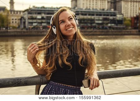 Girl with the headphones and mobile listening to the music or tourist on audio excursion in the city