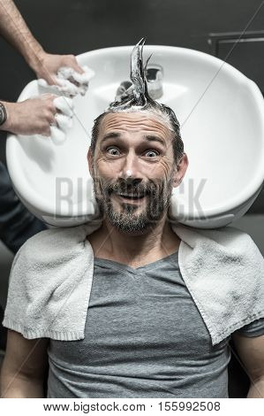 Grimacing man with a beard lies on the white sink in the barbershop. He has the lathered head with the punk hairstyle. Guy wears a gray T-shirt with a white towel. Vertical.