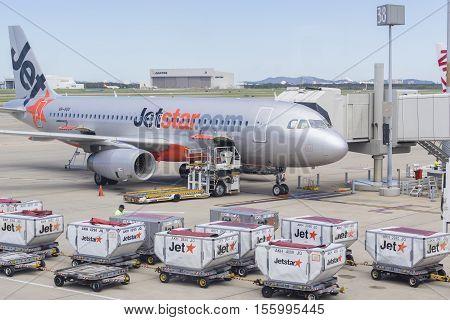 Brisbane, Australia - September 27, 2016: View of baggage trucks waiting to offload passengers' luggage to Jetstar aircraft at Brisbane Airport during daytime.