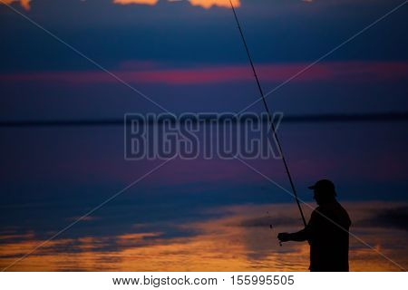 Silhouette of fishermen on the quiet ocean with the rays of sunset.