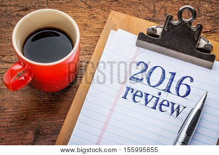 2016 review on clipboard with coffee against grunge wood desk