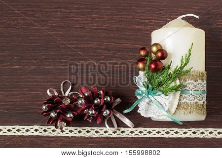 Christmas background with a candle decorated with their own hands. Burlap eco-decor. Ornaments from burlap lace spruce twigs and decorative berries. Empty space for text