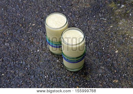 Two healthy drinks yellow mango smoothies on wet concrete reflecting blue sky