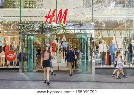 Brisbane, Australia - September 26, 2016: View of a young woman walking out of H and M store in Brisbane. H M is a well-known international fashion retail corporation.