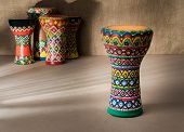 Front view of decorated colorful pottery goblet drum on background of goblet drums, wooden table with vanishing shadow lines, and sackcloth wall. Low light studio shot poster