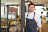 Portrait of smiling owner standing at his restaurant gate with open signboard. Young entrepreneur leaning at the cafeteria door and looking at camera. Chef or waiter standing in front of coffee shop. poster