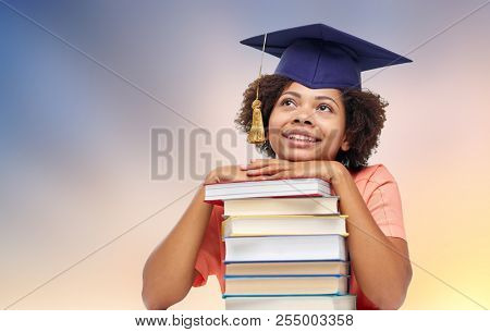 education, school, knowledge and graduation concept - happy smiling african american graduate student girl in mortarboard with books dreaming