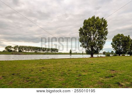 Atmospheric Landscape With The Dutch River Bergsche Maas Near The Village Sprang-capelle. It Is At T