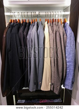 Set of suits with shirts, shoes in shop