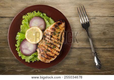Grilled Chicken Fillet With Vegetables (lemon, Salad, Onion) On A Wooden Background. Chicken Fillet