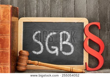 German abbreviation SGB for Sozialgesetzbuch (Sozial Book of law) on chalkboard and paragraph as law concept