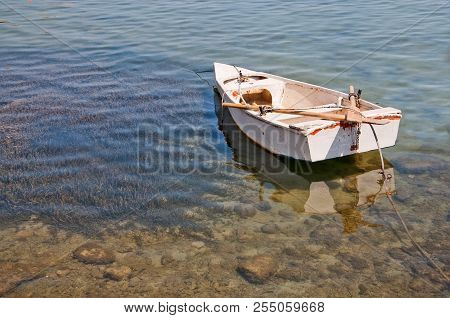 Small Boat Moored In Shallow Water With Protected Seagrass Poseidonis In Mallorca, Spain.