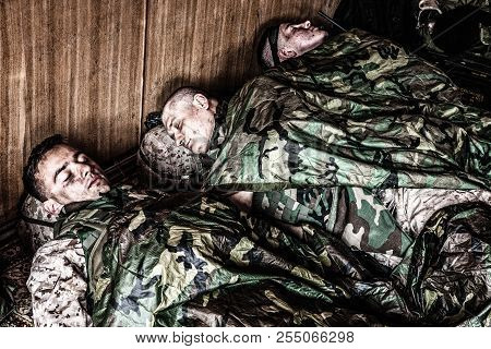 Tired soldiers sleeping on floor at temporary base poster