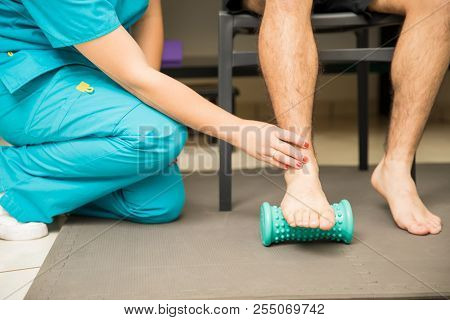 Low section of female therapist assisting patient to use foot roller for plantar fasciitis and pain relief in hospital poster