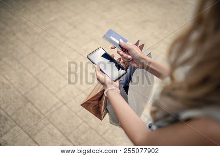 Girl In Shopping. Blonde Woman With Shopping Bags, Credit Card And Phone. Hands Holding Credit Card