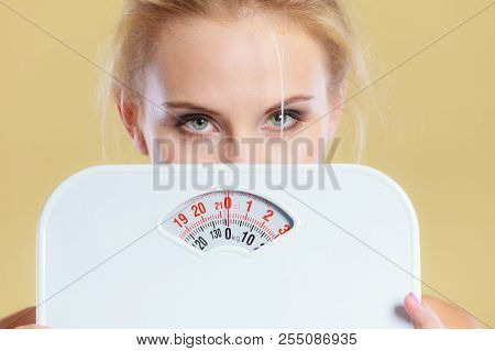 Frustrated sad blonde girl covering her face with scales. Weight gain, time for slimming weightloss, diet. poster