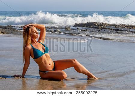 A beautiful blonde model enjoys a day by the beach