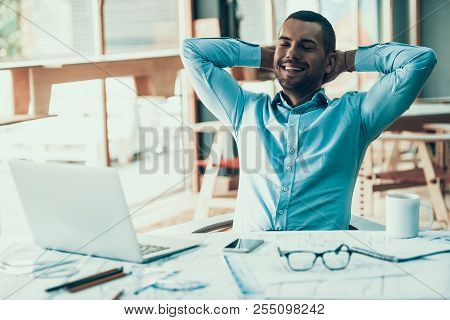 Young Smiling Businessman Resting In Office. Laptop In Office. Businessman Satisfied With Work Done.