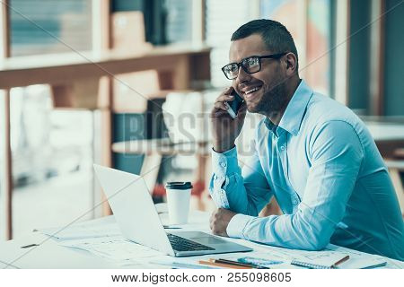 Young Smiling Businessman Working In Office. Laptop In Office. Closeup Of Happy Man Sitting At Desk