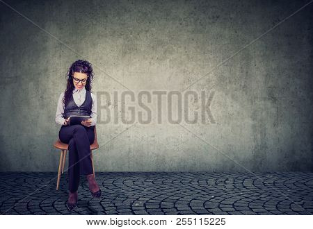 Elegant Woman Sitting On Chair And Using Tablet Being Professional Employee On Gray Background