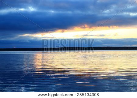 Beautiful sunset. Sunset on the lake. Evening landscape. Clouds reflected in the water. The horizon at sunset. Sea, lake at sunset. The waves on the river. The lake in Russia
